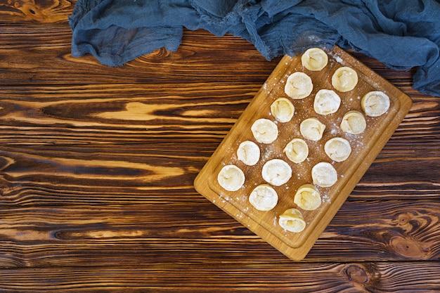 Homemade raw dumplings, pelmeni, on wooden .