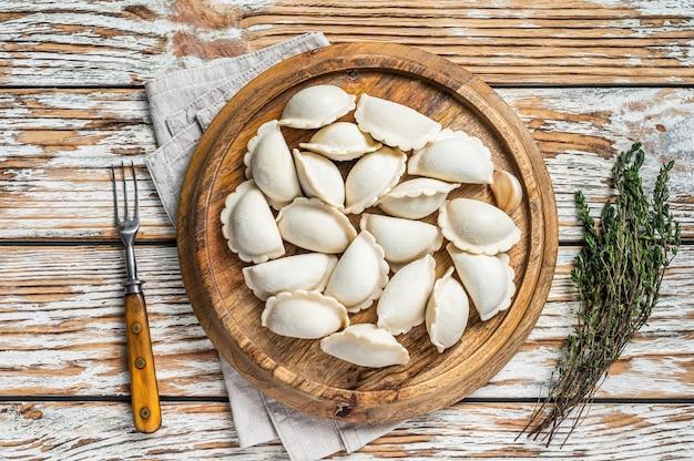 수제 원시 냉동 만두, vareniki, pierogi는 나무 보드에 감자로 채워져 있습니다. 흰색 나무 테이블. 평면도.