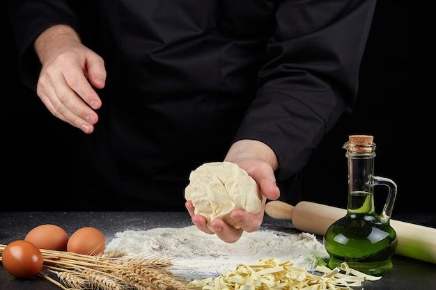 Домашняя сырая лапша из муки, яйца на деревянной миске на черном. руки повара