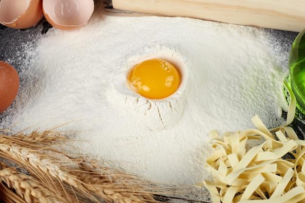 Домашняя сырая лапша из муки, яйца на деревянной миске на черном