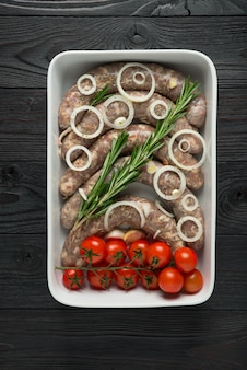 Homemade raw sausages on a wood surface
