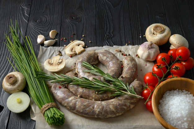 Homemade raw sausages on a wooden surface