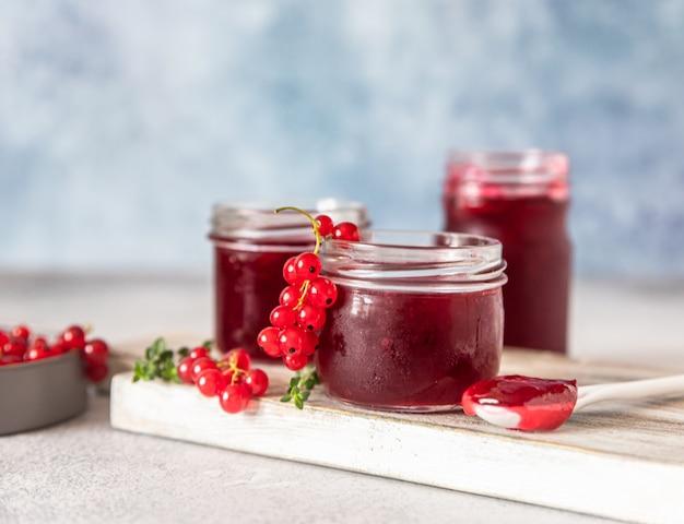 ガラスの瓶に自家製の赤スグリのジャムまたはゼリーとまな板の上の赤スグリの新鮮なベリー