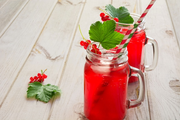 Homemade red currant lemonade in a mason jar with decor of berry on ligth wooden table.