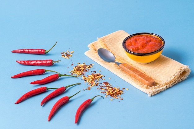 Homemade red harissa paste, chili pepper spices and fresh red chilli peppers.