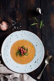베이컨과 오래 된 나무 표면에 흰색 접시에 arugula로 만든 빨간 렌즈 콩 크림 수프. 소박한 스타일. 평면도.