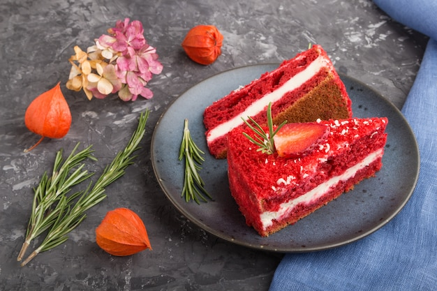 Домашний красный бархатный торт с молочным кремом и клубникой на сером фоне