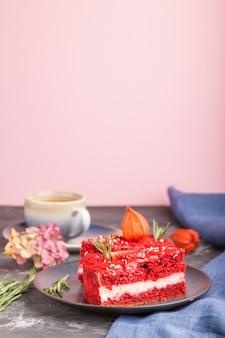 Домашний красный бархатный торт с молочным кремом и клубникой с чашкой кофе на черной и розовой стене. вид сбоку, выборочный фокус, копия пространства.