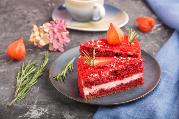 Домашний красный бархатный торт с молочным кремом и клубникой с чашкой кофе на черном фоне
