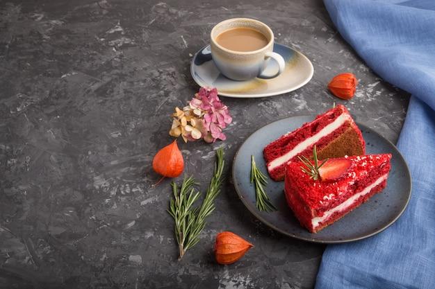 Домашний красный бархатный торт с молочным кремом и клубникой с чашкой кофе на черной бетонной поверхности. вид сбоку, копия пространства.
