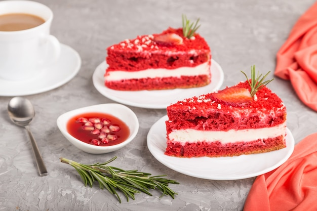 Домашний красный бархатный торт с молочным кремом и клубникой с чашкой кофе на сером бетоне.