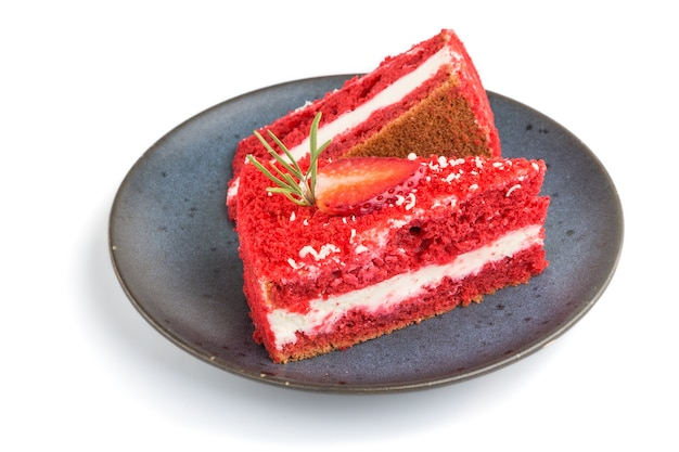 Homemade red velvet cake with milk cream and strawberry on blue ceramic plate isolated. side view, close up. Premium Photo