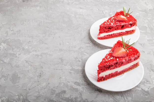 Homemade red velvet cake with milk cream and strawberry on a gray background