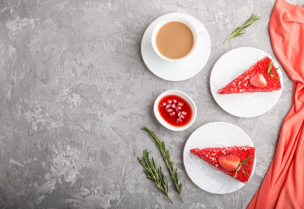 Homemade red velvet cake with milk cream and strawberry  with cup of coffee on a gray concrete background. top view, copy space.