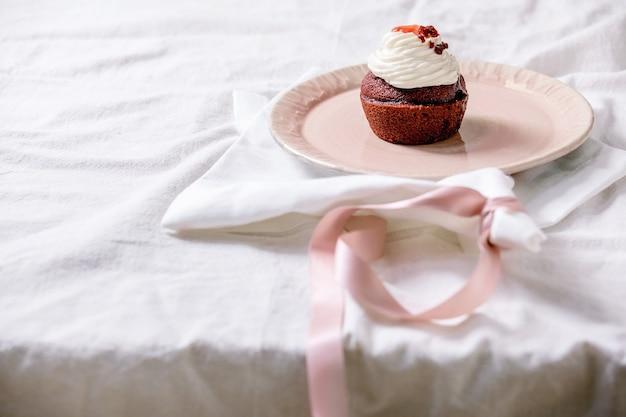 Домашний красный бархатный кекс со взбитыми сливками на розовой керамической тарелке, белая салфетка с лентой на белой льняной скатерти. копировать пространство