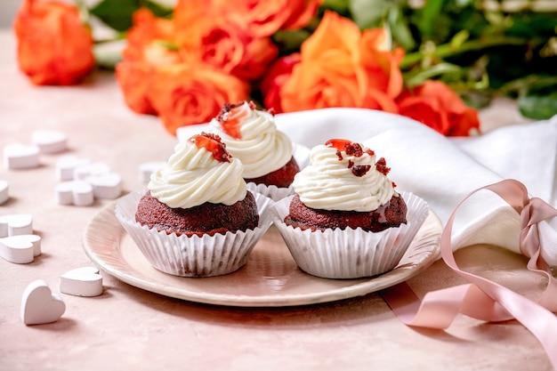 ピンクのセラミックプレートにホイップクリーム、リボン付きの白いナプキン、バラの花、ピンクのテクスチャの壁に木製のハートと自家製レッドベルベットカップケーキ