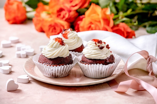 Homemade red velvet cupcakes with whipped cream on pink ceramic plate, white napkin with ribbon, roses flowers, wooden hearts over pink texture wall
