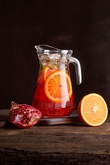 Homemade red wine sangria with orange, pomegranate and ice in glass and pitcher on rustic wooden background. copy space, selective focus. healthy food. photo for the menu