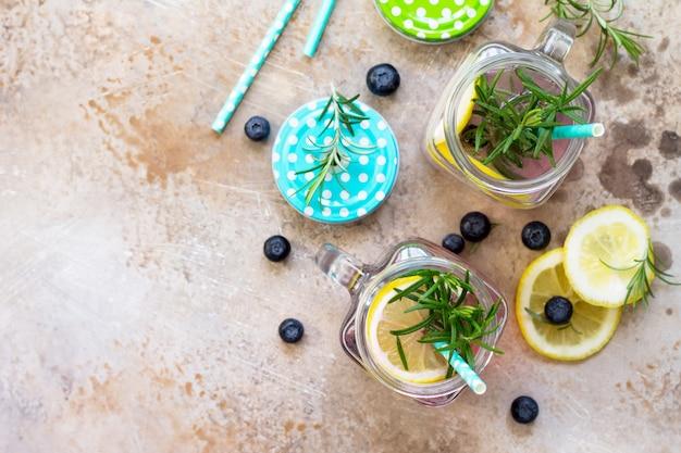적절한 영양의 개념으로 블루베리 레몬과 로즈마리를 곁들인 홈메이드 상쾌한 음료