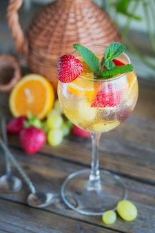 Homemade refreshing fruit sangria or punch with champagne, strawberries, oranges and grapes