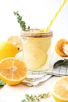 Домашний освежающий лимонад, детокс-напиток с лимоном и зеленью на светлом фоне, крупным планом