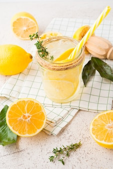 Homemade refreshing lemonade, detox drink with lemon and herbs on a light background, selective focus
