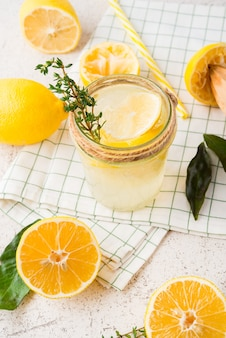 Homemade refreshing lemonade, detox drink with lemon and herbs on a light background,selective focus
