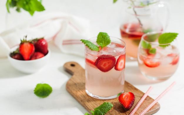 신선한 딸기와 민트 잎을 가진 안경과 용기에 수제 상쾌한 딸기 레모네이드