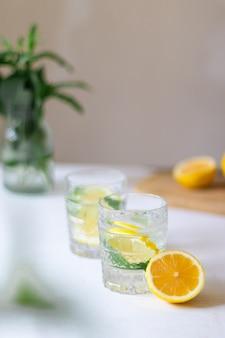 배경에 꽃병에 꽃다발과 함께 안경에 레몬 조각과 얼음을 곁들인 홈메이드 여름 레모네이드 음료