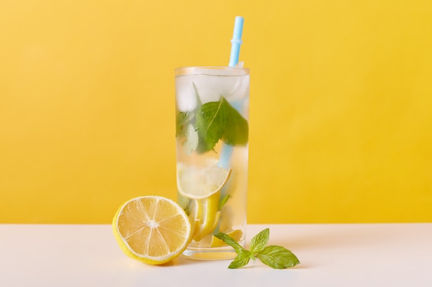 Homemade refreshing summer lemonade drink with lemon slices, mint and ice cubes