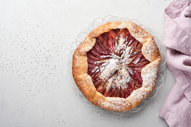 Самодельный галет из ревеня с звездным рисунком на фоне старого бетонного стола. процесс запекания. открытый пирог. рождественская и новогодняя выпечка. вид сверху домашней корочки пирога на столе.