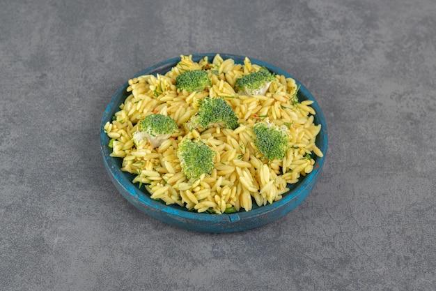 Домашний рис с брокколи на голубой тарелке. фото высокого качества
