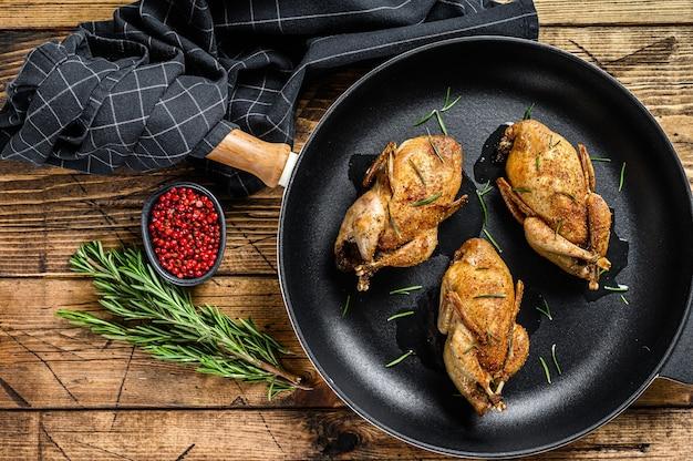Домашний жареный перепел голубя на сковороде. деревянный фон. вид сверху.
