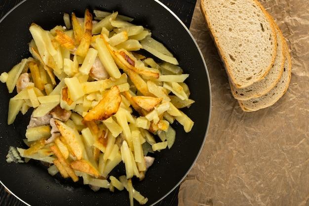 Домашний жареный картофель в сковороде на деревенском фоне крупным планом и вид сверху.
