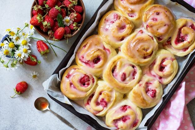 석재 배경에서 아침 식사로 유약에 크림 치즈와 딸기를 곁들인 홈메이드 롤빵