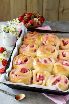 아침 식사로 유약에 크림 치즈와 딸기를 곁들인 홈메이드 롤빵