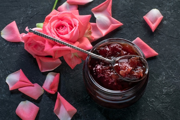 Homemade rose petal jam on black surface