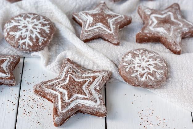 白い木製のテーブルに自家製の丸くて星型のクリスマスジンジャーブレッドクッキー