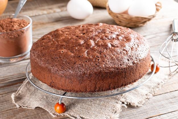 집에서 만든 둥근 초콜릿 스폰지 케이크 또는 쉬폰 케이크는 계란, 밀가루, 코코아, 나무 탁자에 있는 우유 등의 재료로 부드럽고 맛있습니다. 배경 및 벽지에 대한 수제 베이커리 개념