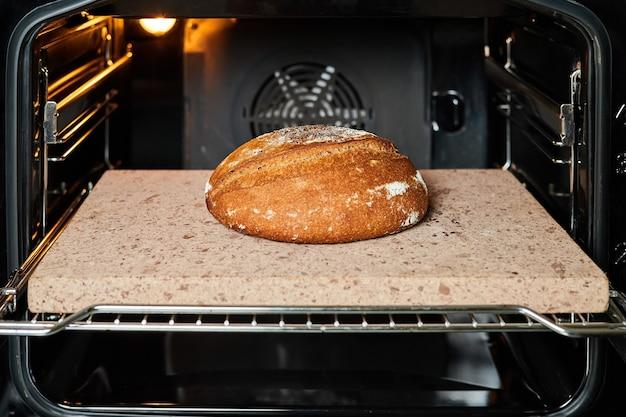 Домашний круглый ржаной хлеб выпекается в духовке на камне.
