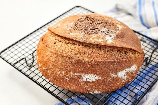 布で金属ワイヤーラックに自家製の丸いライ麦パン