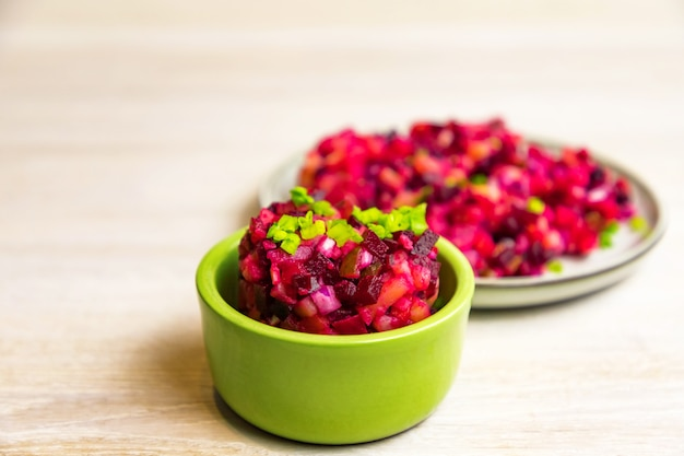 Homemade russian beet salad in green bowl and grey plate on white table background. close up. selective focus. copy space