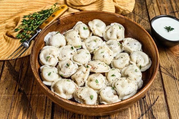 나무 그릇에 쇠고기와 돼지 고기로 만든 러시아 만두 pelmeni.