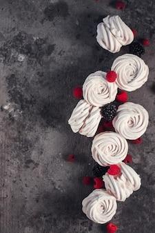 暗い灰色のコンクリートの上にリンゴ、ラズベリー、ブラックベリーで作られた自家製のロシアのゼファー