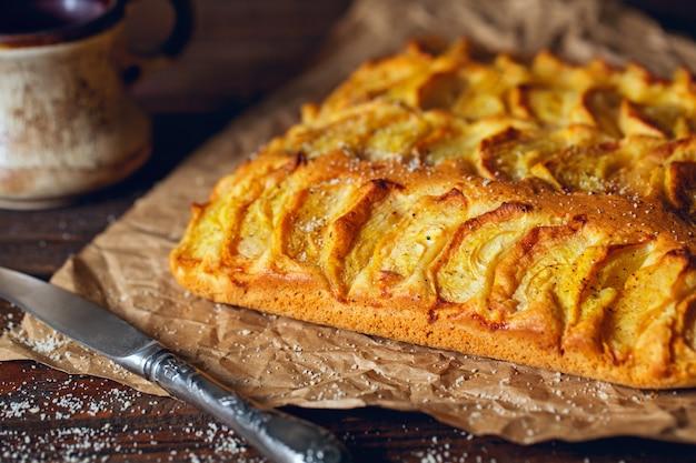 Домашний деревенский яблочный пирог на деревянном старом винтажном столе.