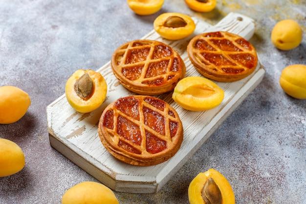 Mini torta o crostate di albicocche rustiche fatte in casa con frutta fresca all'albicocca.