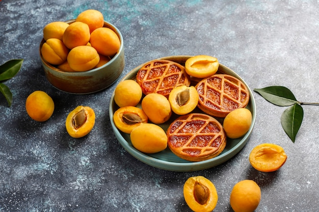 Homemade rustic mini apricot tarts with fresh apricot fruits.