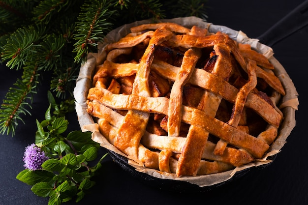 Homemade rustic organic apple pie in iron skillet pan decorate by pine leaf on black slate stone board