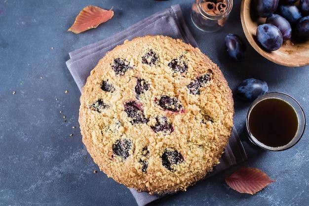 Homemade rustic plum cake on dark concrete table. sweet fruits pie.