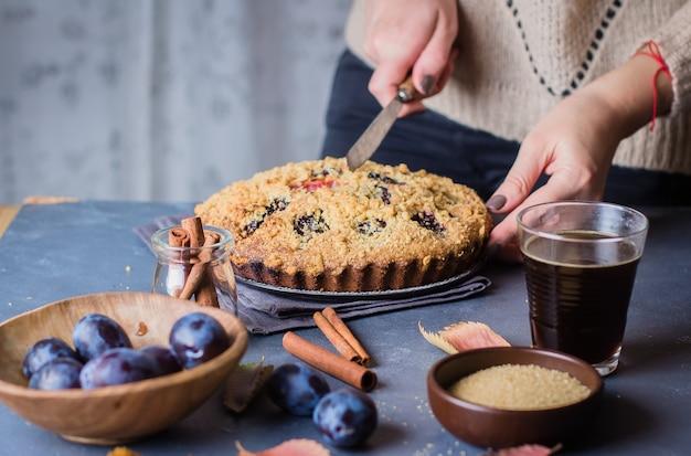 Домашний деревенский сливовый торт на темном бетонном столе. сладкий фруктовый пирог.